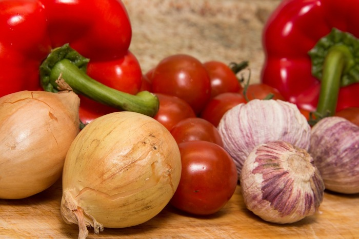 red peppers, onions, tomatoes on a chopping board