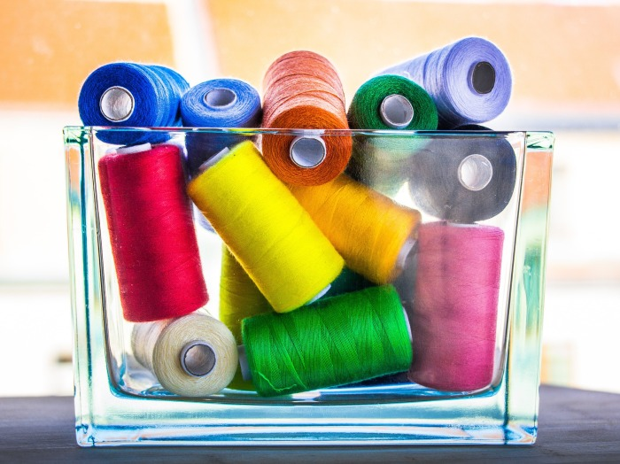 colorful threads in transparent container