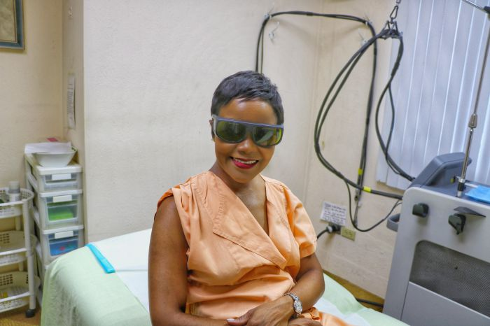Black woman of color wears protective goggles at doctor's office